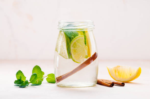 flasche mit entgiftungswasser mit kalk, zitrone, zimt und minze - zimt gurken stock-fotos und bilder