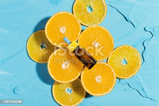 Bottle with essential oil orange, lies on fresh oranges