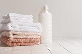 洗濯と木製のテーブルに新鮮なタオルのスタックのためのゲルの瓶