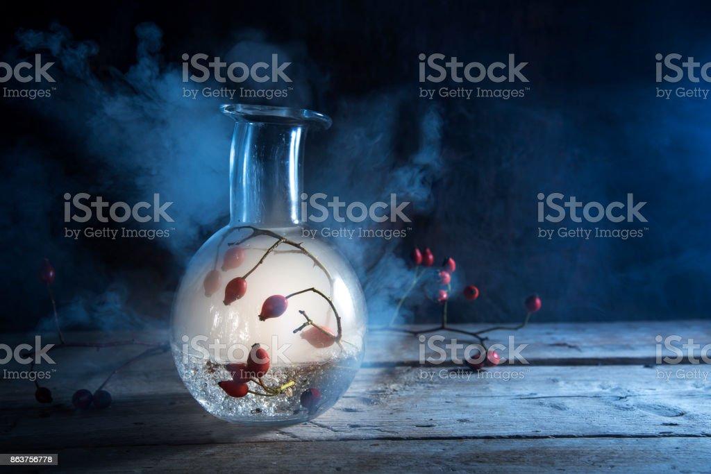 Flasche mit glühenden Rauch und rose Hüfte innen auf einem rustikalen Holztisch gegen einen dunkelblauen Hintergrund, geheimnisvolle Halloween Alchemie, Stillleben mit Textfreiraum – Foto
