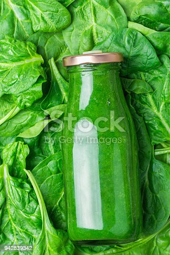 istock Bottle with Green Fresh Raw Smoothie from Leafy Greens Vegetables Fruits Apples Bananas Kiwi Zucchini on Spinach Leaves as Background. Healthy Lifestyle Detox Vitamins Energy Concept. 942839342
