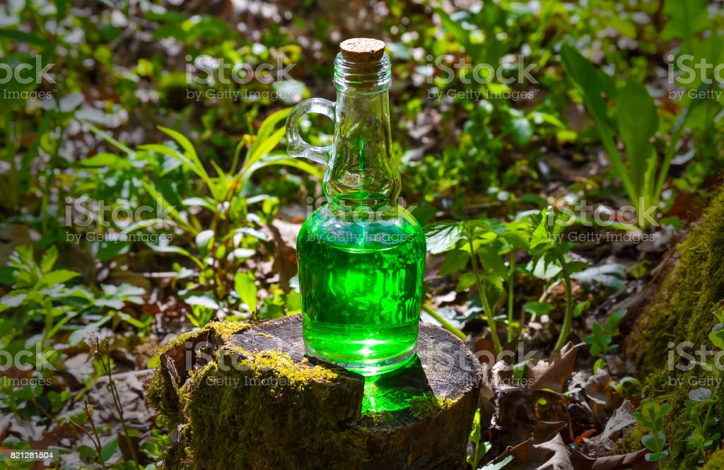 Bottle with green liquid on a stump on a sunny day. stock photo
