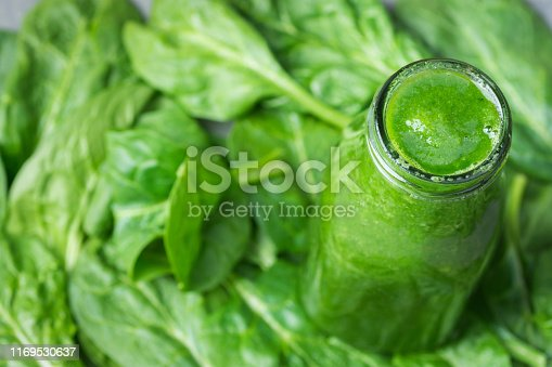 istock Bottle with green raw smoothie from vegetables fruits apples bananas kiwi zucchini on spinach leaves. Healthy plant based diet detox vitamins energy concept 1169530637