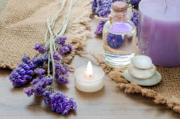Botella con aceite esencial de lavanda, vela sobre mesa de madera. - foto de stock
