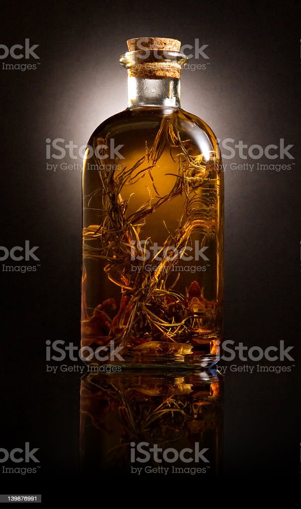 Bottle with oil and aromatic herbs royalty-free stock photo