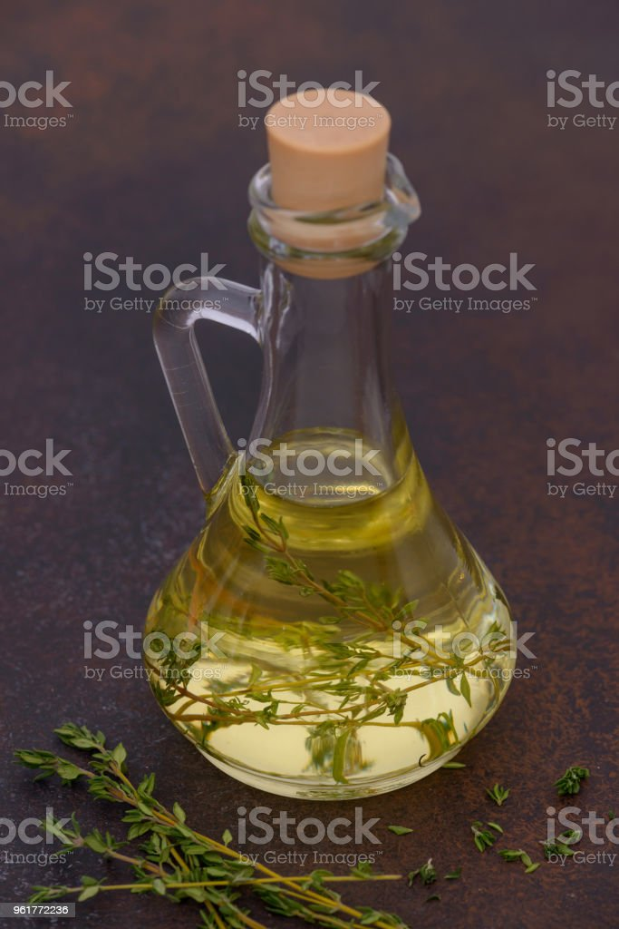 Bottle with olive oil and thyme on table stock photo