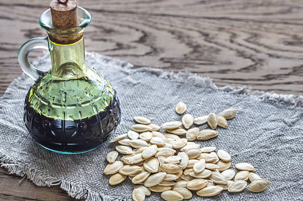 Bottle with pumpkin oil on the wooden background stock photo