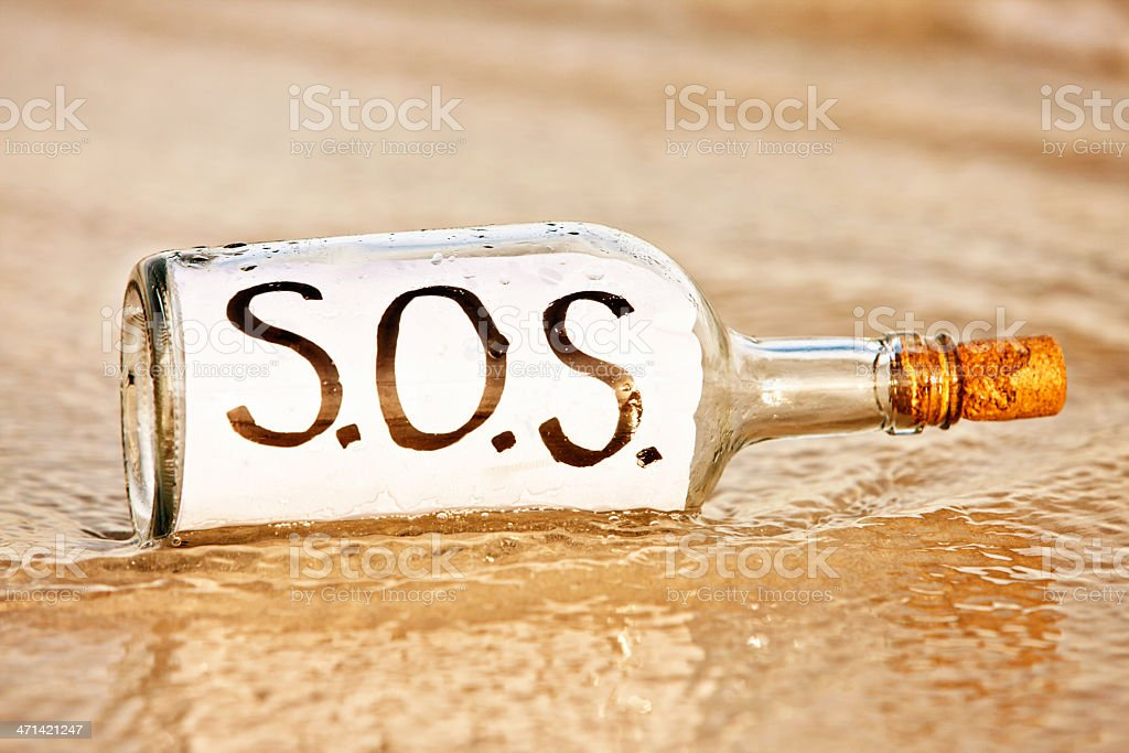 Bottle with SOS message is about to be washed away royalty-free stock photo