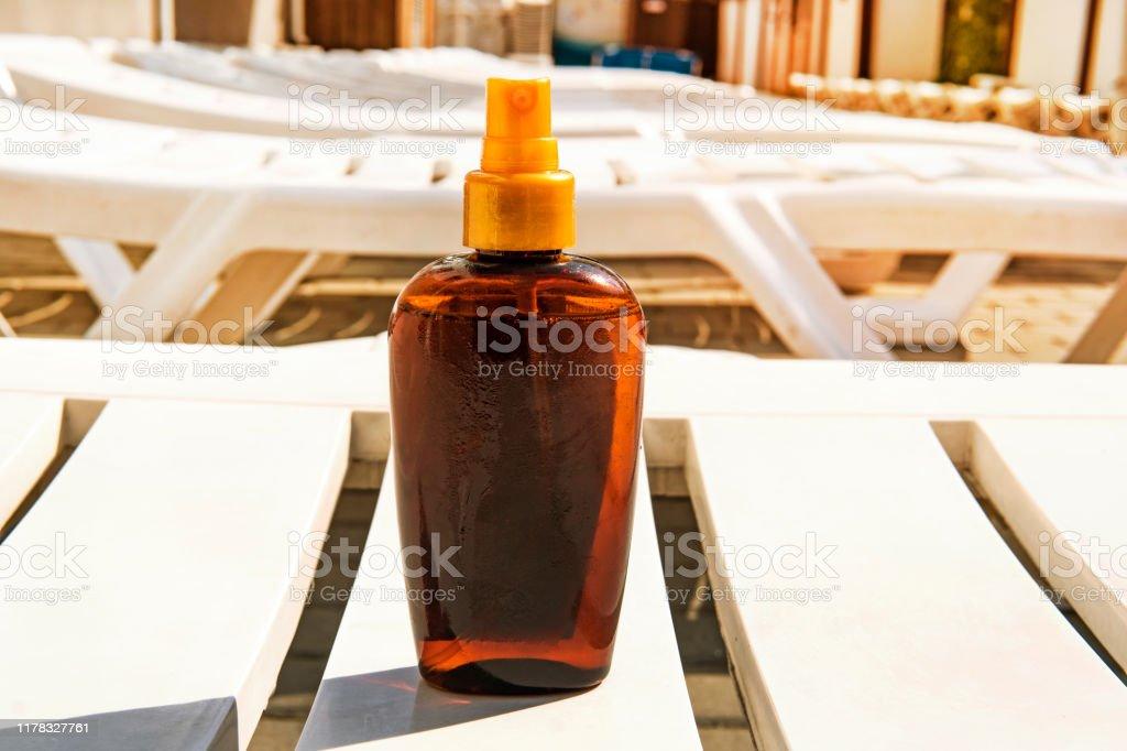 Bottle with suntan cream on white deckchair. Sunburn and cancer...
