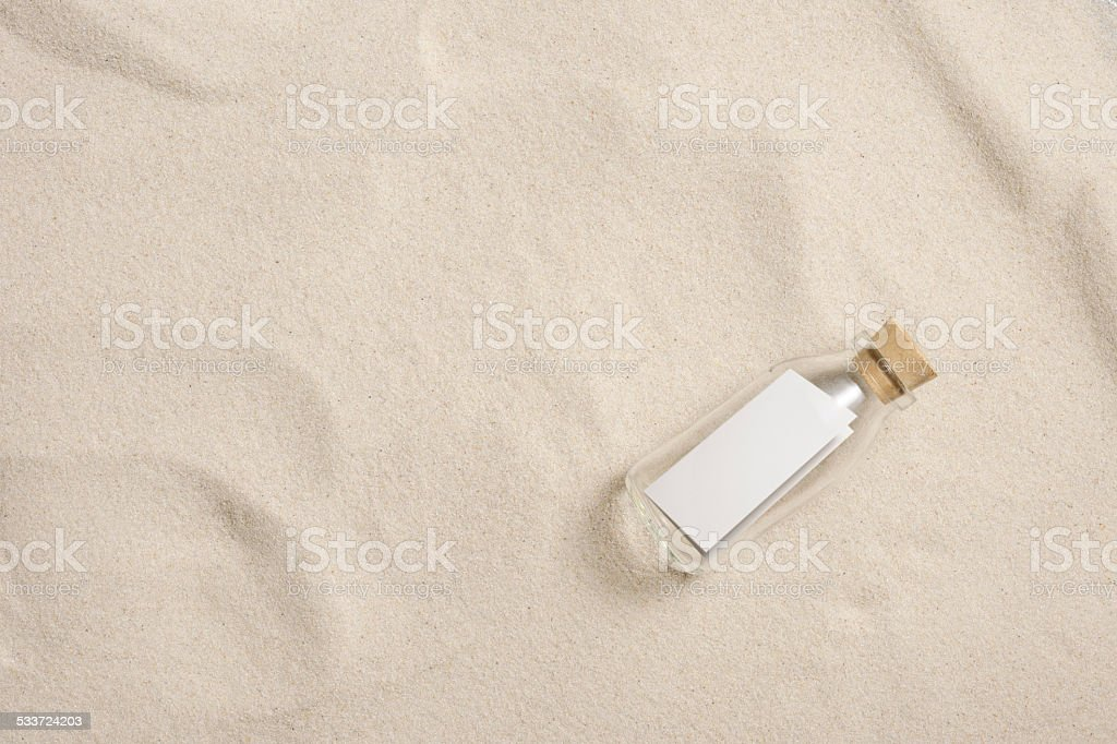 Bottle with the letter on sandy beach with copy space stock photo