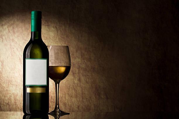 Flasche mit Weißwein und Glas auf einem alten Stein – Foto
