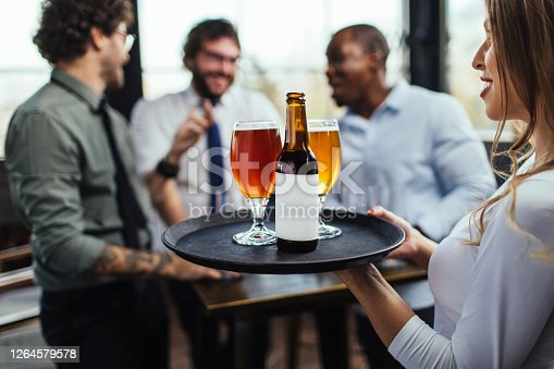 Photo of a young waitress bringing three beers to a group of friends in a bar