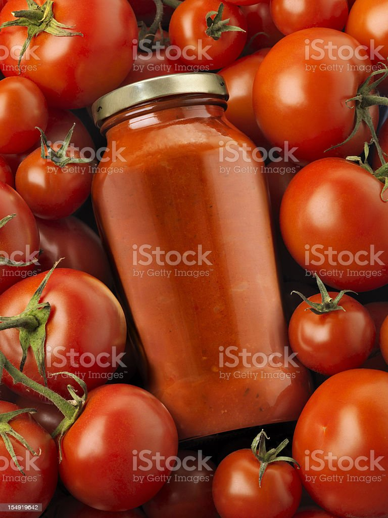 Bottled pasta sauce surrounded by tomatoes stock photo