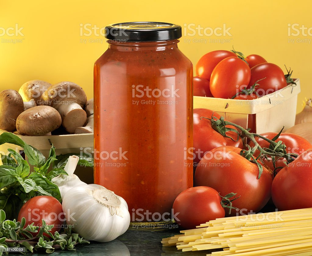 Bottled pasta sauce with raw ingredients stock photo