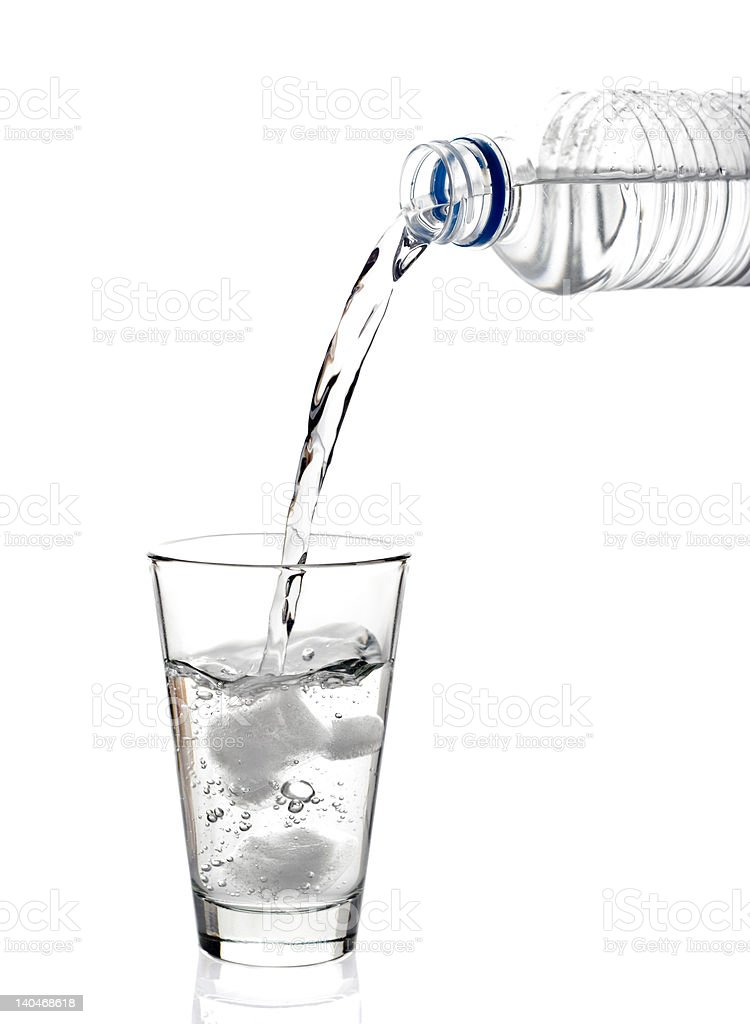 Bottled water being poured into a glass royalty-free stock photo