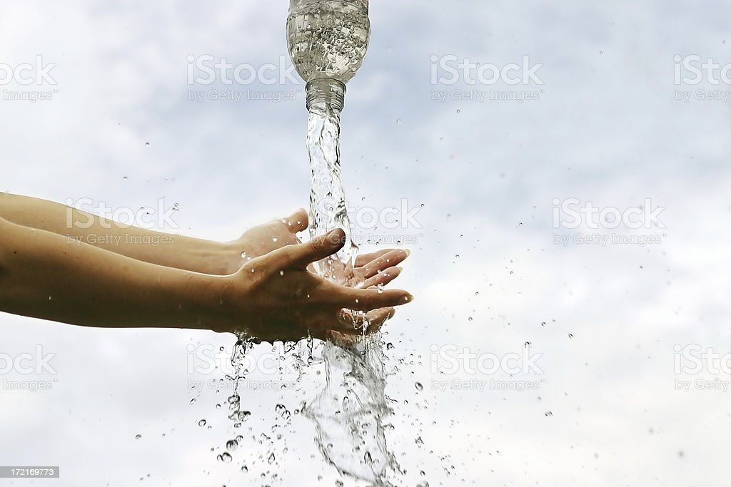 Bottled water splashing on hands. royalty-free stock photo