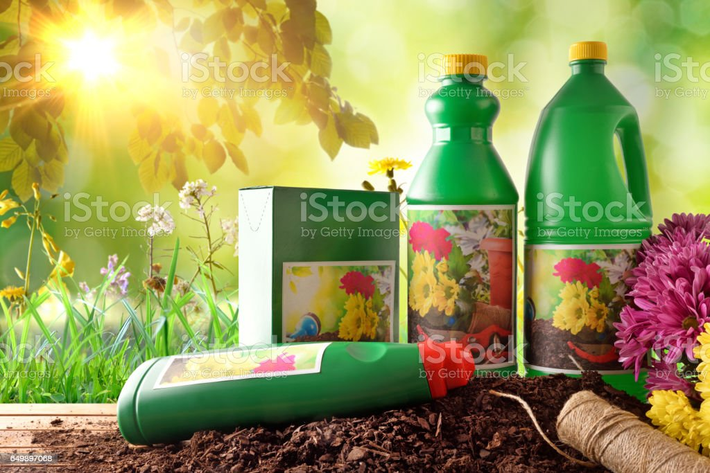 Bottles and containers of gardening products in nature with sunlight stock photo