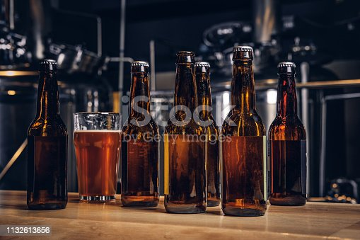 istock Bottles and glass of craft beer on wooden bar counter at the indie brewery. 1132613656