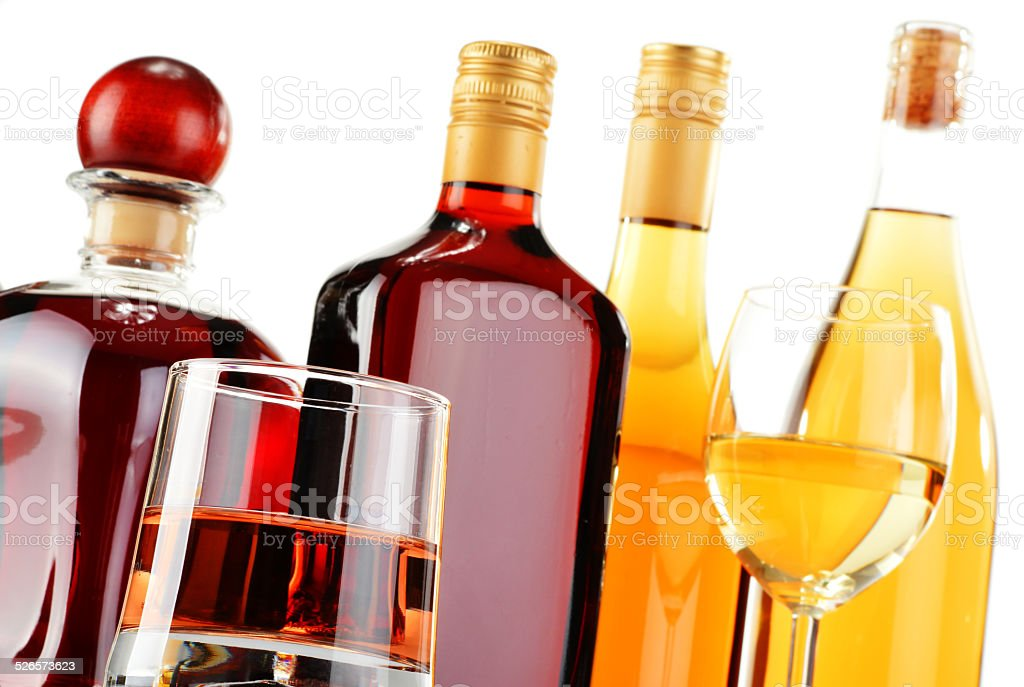 Bottles and glasses of assorted alcoholic beverages over white stock photo