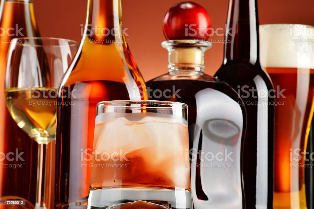 Bottles and glasses of assorted alcoholic beverages stock photo