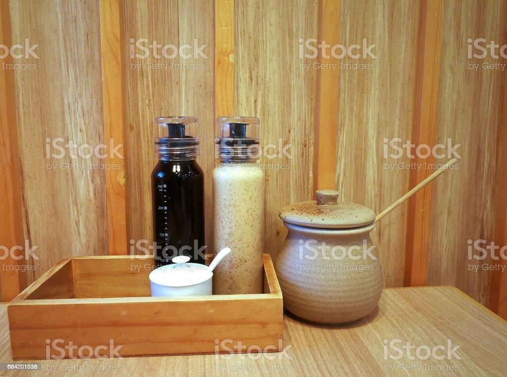 Bouteilles et pot de condiments japonais sur fond en bois photo libre de droits
