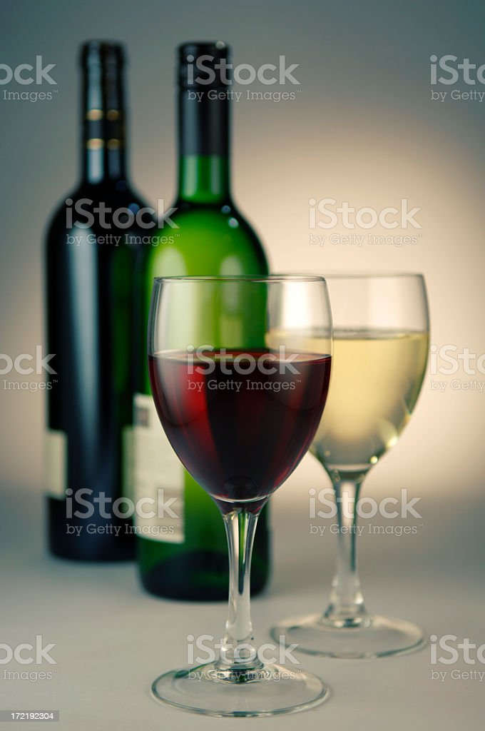 A wine glass full of red wine in front of a glass of white wine. Both...