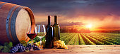 Bottles And Glasses With Ripe Grapes And Wooden Barrel At Sunset