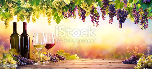 Bottles And Wineglasses With Grapes At Sunset