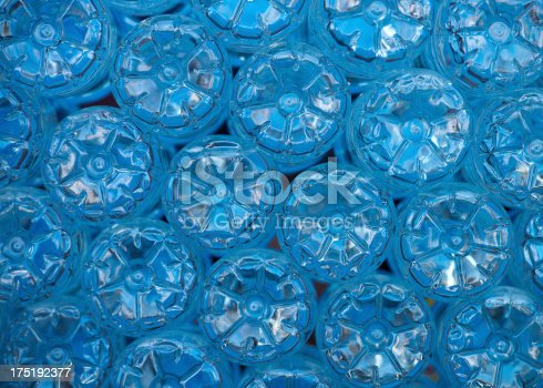 The bottom of empty mineral water bottles covered with drops. Focus is only on one.