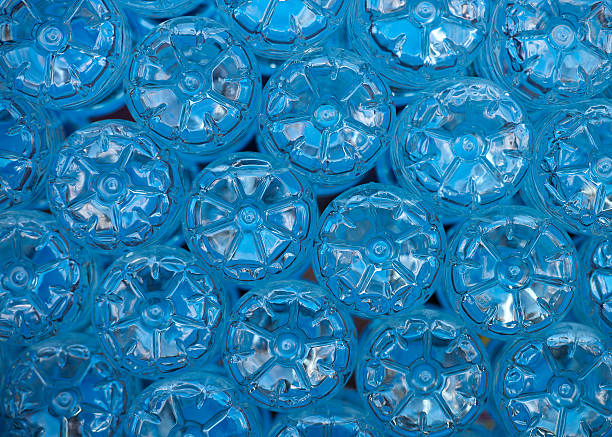 bottles background The bottom of empty mineral water bottles covered with drops. Focus is only on one. at the bottom of stock pictures, royalty-free photos & images