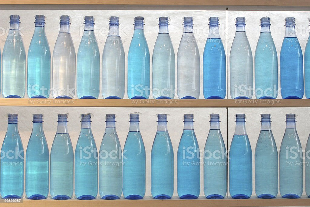 Bottles filled with water, standing on the shelf - Royalty-free Blue Stock Photo
