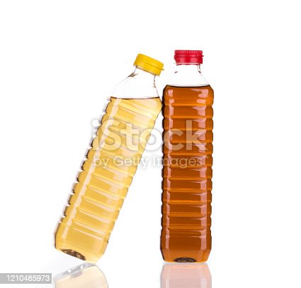 Bottles full of vinegar and cooking oil. Isolated in a white background. Close-up.