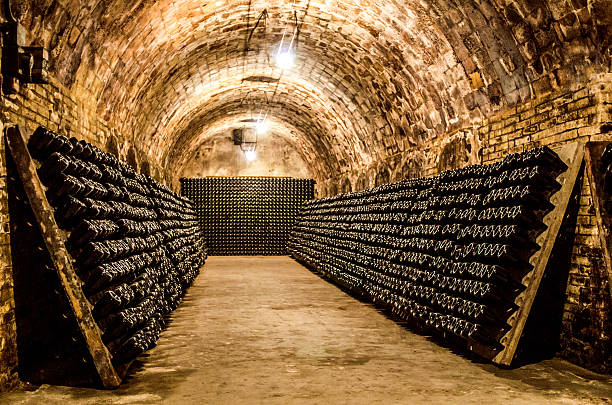 bottles in a cellar horizontal champagne (cava) bottles maturing in cellar cellar stock pictures, royalty-free photos & images