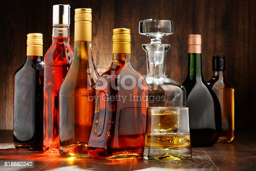 Composition with bottles of assorted alcoholic beverages.