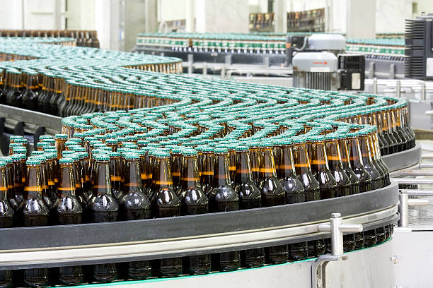 bottles of beer on conveyor in brewery - bottling plant stock photos and pictures