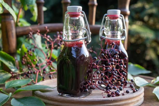 bottles of black elder syrup with fresh elderberries - xarope imagens e fotografias de stock