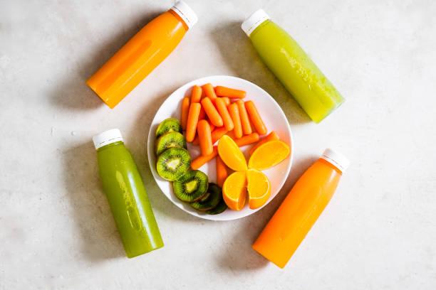 bouteilles de froids jus pressés avec des fruits et légumes - cold pressed photos et images de collection