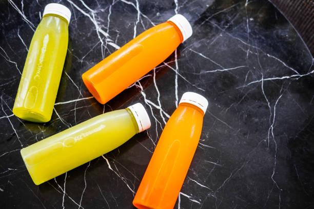 bouteilles de jus de première pression à froid sur table de marbre - cold pressed photos et images de collection