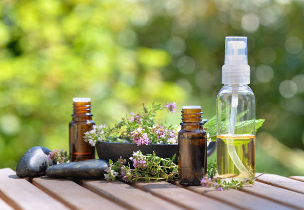 botellas de aceite esencial y flores de hierba aromática sobre atable y sobre fondo verde - foto de stock