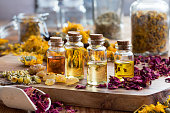 istock Bottles of essential oil with dried rose petals, chamomile, calendula and frankincense 899747886