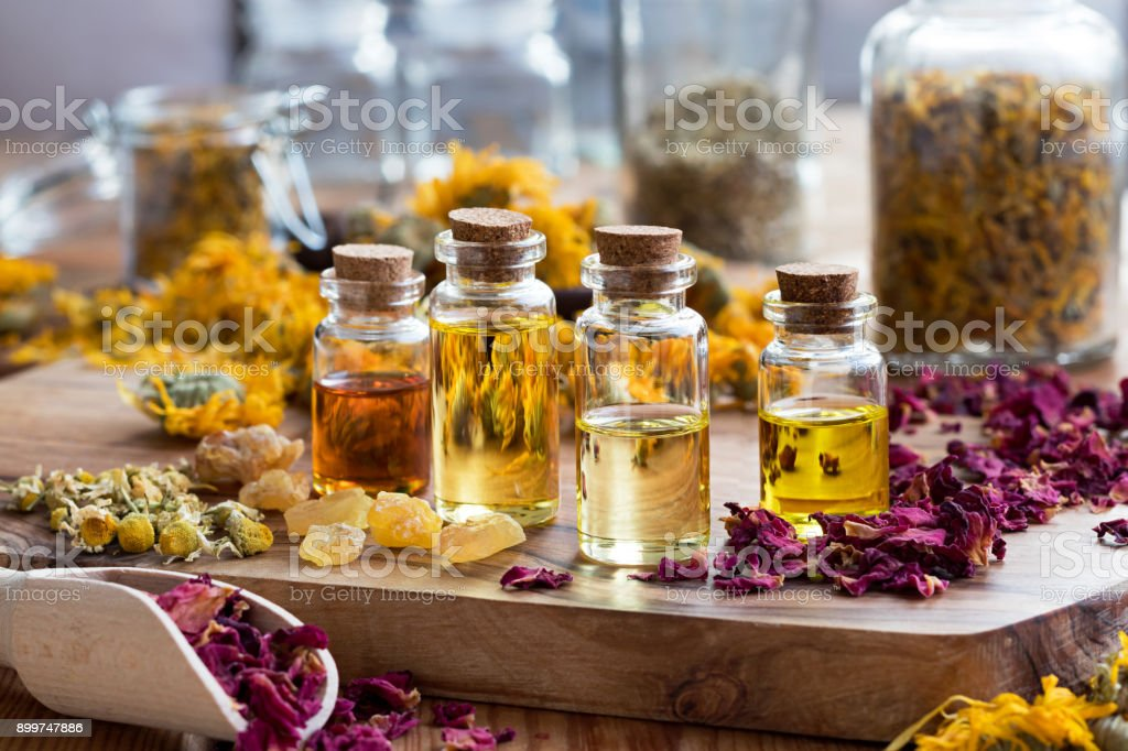 Bottles of essential oil with dried rose petals, chamomile, calendula and frankincense - foto stock