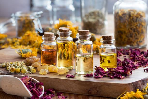 bottles of essential oil with dried rose petals, chamomile, calendula and frankincense - profumi foto e immagini stock