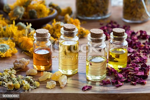 istock Bottles of essential oil with dried rose petals, chamomile, calendula and frankincense 900990692