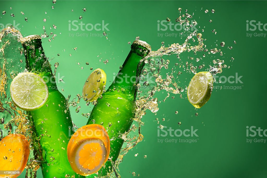 Bottles of fruit beer with splash, on gree stock photo