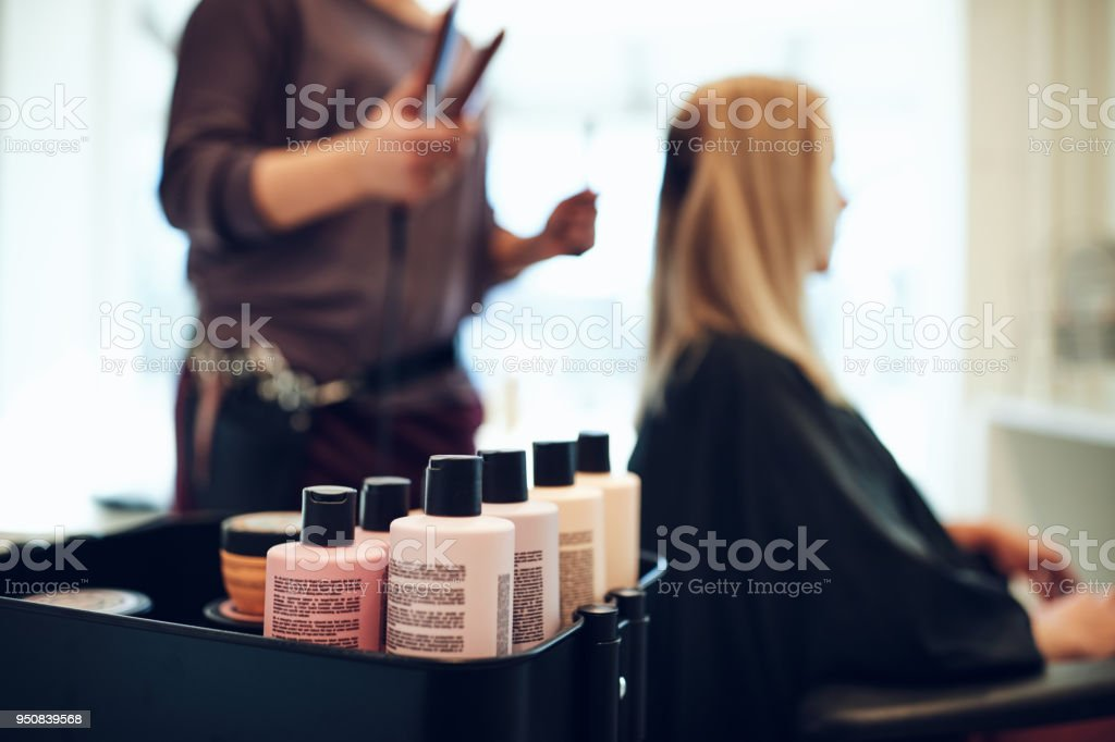 Closeup of shampoo and conditioner bottles on a tray in a hair salon...