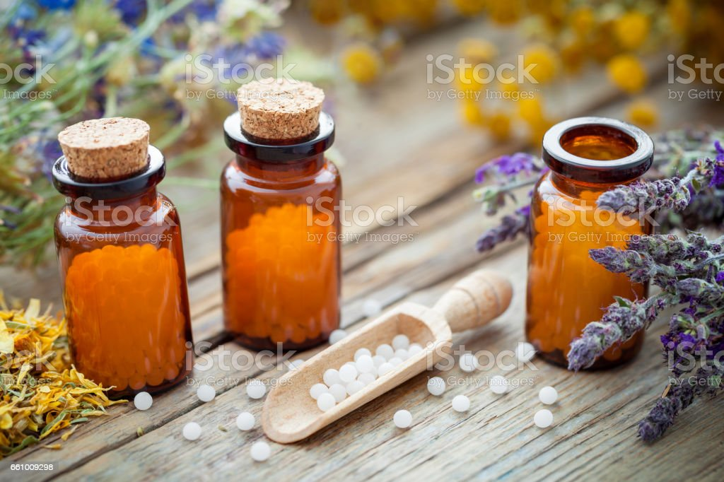 Bottles of homeopathic globules and healing herbs. Homeopathy concept. stock photo