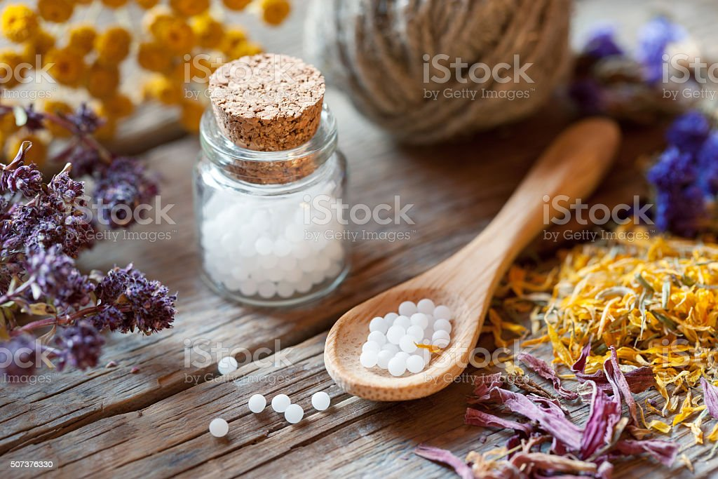 Bottles of homeopathy globules, spoon and healthy herbs. stock photo