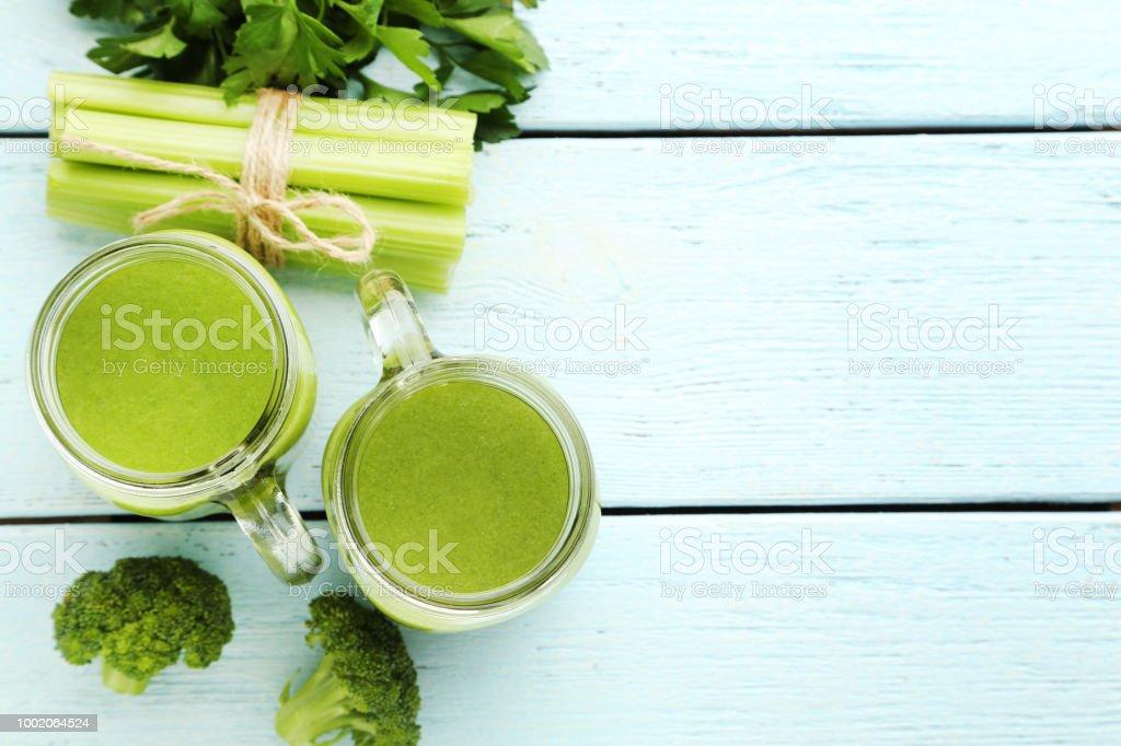 Botellas de jugo con brócoli y apio en mesa de madera blanca - foto de stock