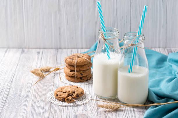 flaschen milch und kekse mit schokosplittern auf hölzernen hintergrund - spitzenkekse stock-fotos und bilder