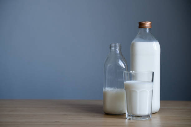 bottles of milk and full glass on light colored wooden table stock photo
